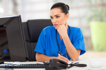 thoughtful medical doctor looking at computer screen in office